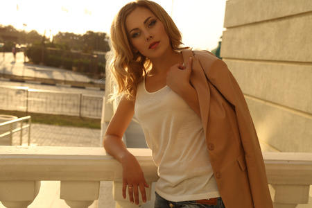 beautiful model: fashion outdoor photo of beautiful young woman with blond hair wears casual clothes posing on balcony