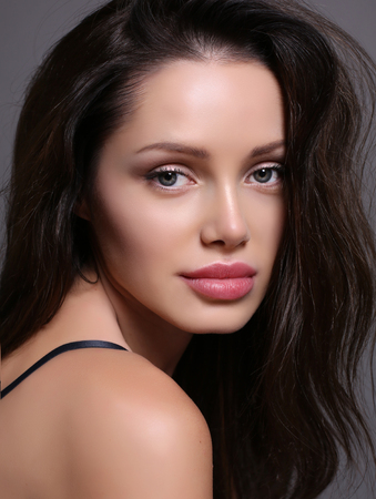 lips glow: fashion studio portrait of beautiful young woman with dark hair and charming smile, with perfect glowing skin