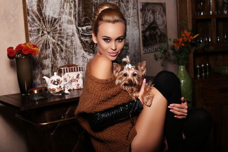 animal woman: fashion interior photo of beautiful woman with blond hair wears casual clothes, posing with cute Yorkshire terrier in cozy home