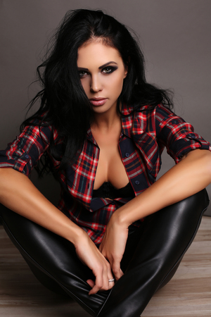 black pants: fashion studio portrait of beautiful woman with long dark hair and bright makeup, wears black lingerie,leather pants  and cosy shirt