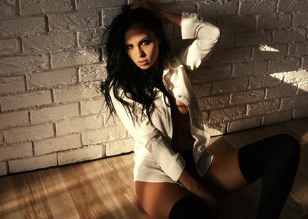 fashion studio portrait of beautiful woman with long dark hair and bright makeup, wears elegant white shirt Stock Photo
