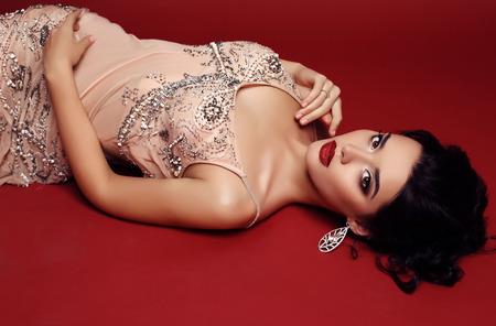 belle brune: studio photo de mode de femme magnifique avec des cheveux noirs porte robe de sequin luxueux et bijou