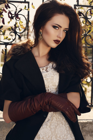 ladylike: fashion outdoor photo of beautiful ladylike woman with dark hair wearing elegant coat with fur and leather gloves