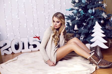 decorated: fashion studio photo of beautiful girl with long blond hair posing beside a decorated Christmas tree