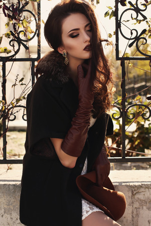 fashion outdoor photo of beautiful young woman with dark hair wearing elegant coat with fur and leather gloves