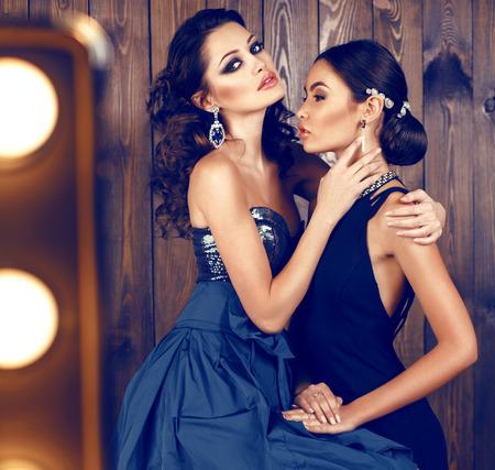 mujeres fashion: moda foto de estudio de dos hermosas mujeres sensuales con el pelo oscuro en vestidos de lujo con bijou Foto de archivo