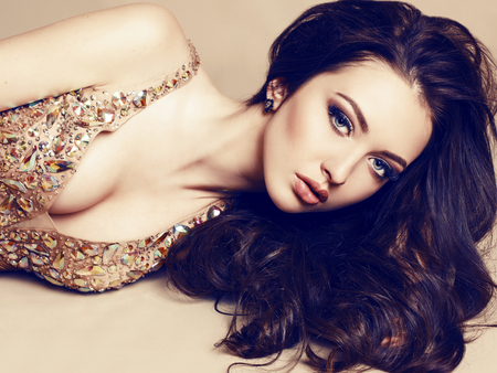 donne eleganti: Studio moda ritratto di giovane e bella ragazza con i capelli scuri lusso di indossare abito beige