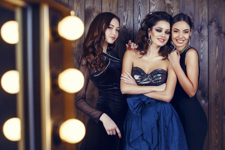bijou: fashion studio photo of three beautiful smiling girls in luxurious dresses and bijou Stock Photo