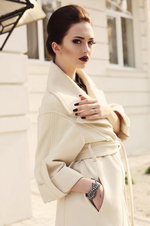 ladylike: fashion outdoor photo of beautiful ladylike woman with dark hair and bright makeup,wearing elegant beige coat Stock Photo