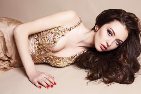 fashion studio portrait of beautiful young girl with dark hair wearing luxurious beige dress
