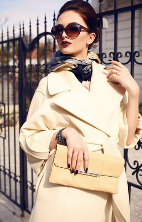 fashion outdoor photo of beautiful elegant lady wearing luxurious beige coat and sunglasses