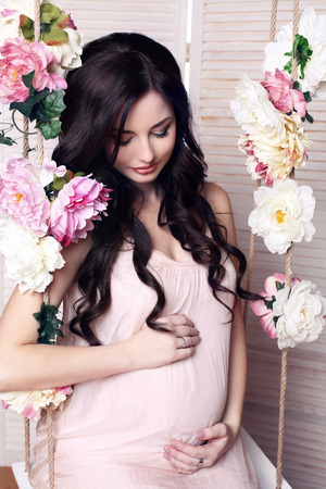 cosily: fashion photo of beautiful pregnant woman with long dark hair posing in cozy interior Stock Photo