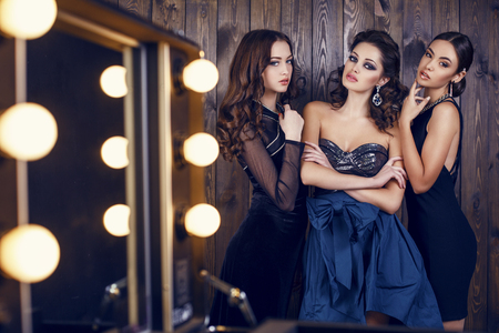 woman hairstyle: fashion studio photo of  beautiful sensual women with dark hair in luxurious dresses with bijou, posing in makeup room