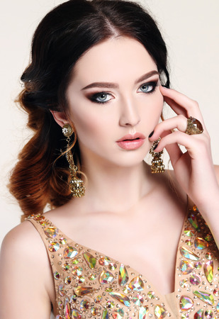 gold necklace: fashion studio photo of beautiful sensual woman with dark hair wearing luxurious sequin dress and bijou