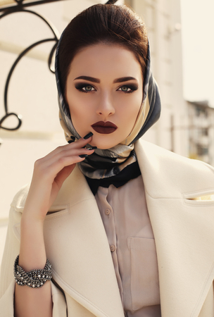 chic woman: fashion outdoor photo of beautiful elegant lady wearing luxurious beige coat and silk scarf on her head