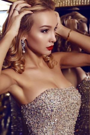 mujer elegante: Foto de la moda de la mujer hermosa con el pelo rubio en un elegante vestido posando en el interior de lujo Foto de archivo