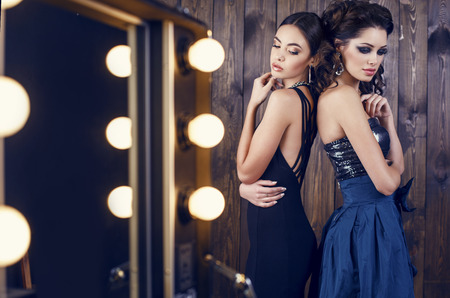 fashion studio photo of two beautiful sensual women with dark hair in luxurious dresses with bijou 스톡 콘텐츠