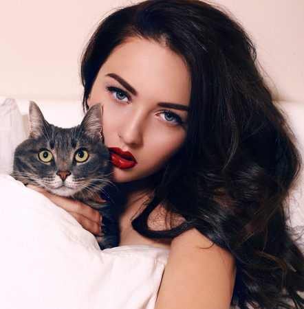 beautiful woman body: fashion portrait of beautiful young woman with long dark hair with blue eyes and red lips,lying in bed,holding a cat Stock Photo