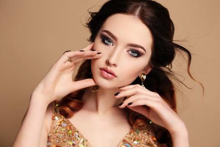 mujeres elegantes: estudio de moda foto de la hermosa mujer sensual con el pelo oscuro con un vestido de lentejuelas de lujo y bijou