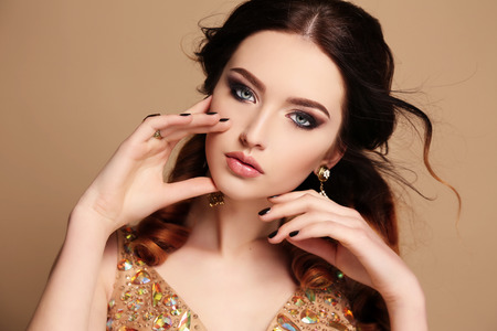 chic woman: fashion studio photo of beautiful sensual woman with dark hair wearing luxurious sequin dress and bijou