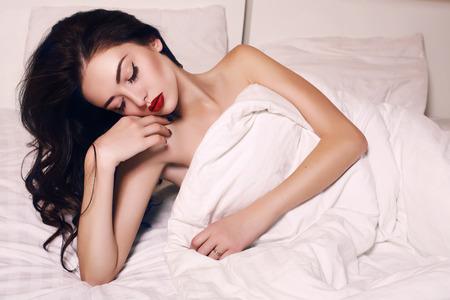 fashion interieur foto van mooie jonge vrouw met donker haar en lichte make-up liggend in bed op slaapkamer Stockfoto