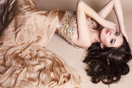 fashion: 豪華なベージュのドレスを着ている黒髪の美しい若い女の子のファッション スタジオ写真