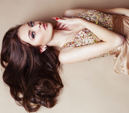 glamour hair: fashion studio portrait of beautiful young girl with dark hair wearing luxurious beige dress