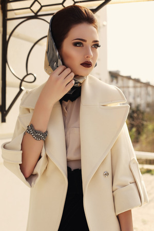 head scarf: fashion outdoor photo of beautiful elegant lady wearing luxurious beige coat and silk scarf on her head