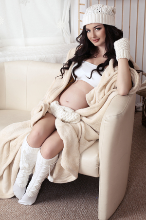 long socks: fashion photo of beautiful pregnant woman with long dark hair wearing warm knitted clothes posing in cozy interior