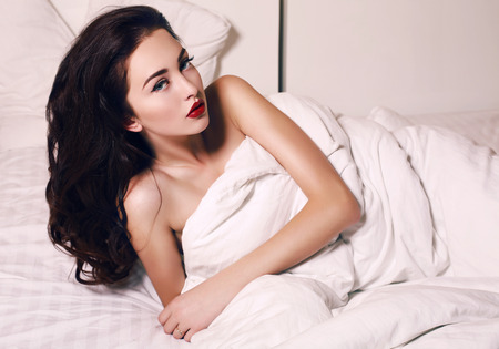 woman in bed: fashion interior photo of beautiful sensual woman with dark hair and blue eyes lying in bed at bedroom Stock Photo