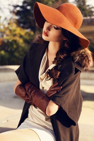ladylike: fashion outdoor photo of beautiful ladylike woman with dark hair wearing elegant coat with fur,felt hat and leather gloves