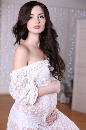 cosily: fashion photo of beautiful pregnant woman with long dark hair wearing lace dress Stock Photo