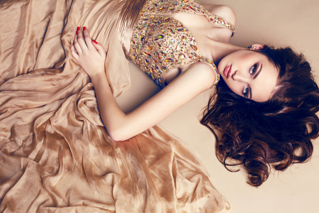 fashion photo of beautiful young girl with dark hair wearing luxurious beige dress,lying on the floor at studio