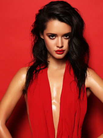 fashion studio portrait of gorgeous sensual woman with dark hair wears elegant red dress Standard-Bild