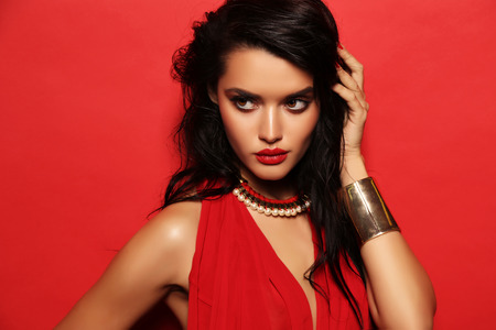 red dress: fashion studio portrait of gorgeous sensual woman with dark hair wears elegant red dress and accessories