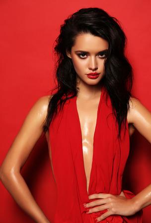 Fashion studio portret van prachtige sensuele vrouw met donker haar draagt elegante rode jurk Stockfoto