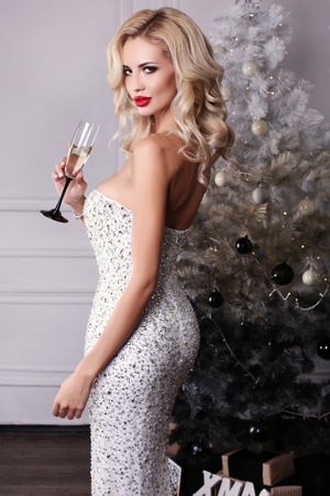 sexy girl posing: fashion interior photo of beautiful sexy girl with blond hair wears luxurious dress,holding glass of champagne in hand,posing near Christmas tree