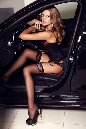 car accessory: fashion photo of gorgeous woman with long blond hair wears luxurious lingerie,posing in car Stock Photo
