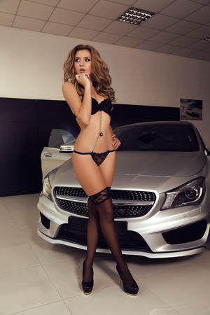 car model: fashion photo of gorgeous woman with long blond hair wears luxurious lingerie,posing beside a car