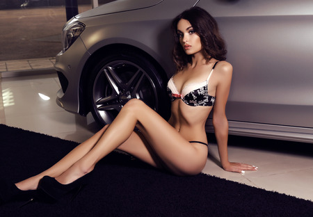 car accessory: fashion photo of gorgeous woman with long dark hair wears luxurious lingerie,posing beside a car