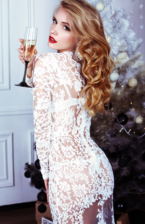 fashion interior photo of beautiful sexy girl with blond hair wears luxurious dress,holding glass of champagne in hand,posing near Christmas tree