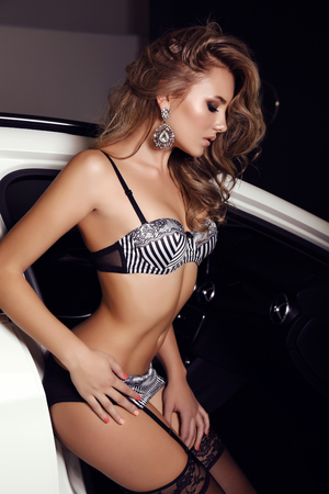 car accessory: fashion photo of gorgeous woman with long blond hair wears luxurious lingerie,posing beside a car