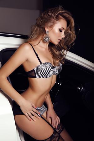 pantimedias: Foto de la manera de la mujer magnífica con el pelo largo y rubio que desgasta la ropa interior luxuus, posando al lado de un coche