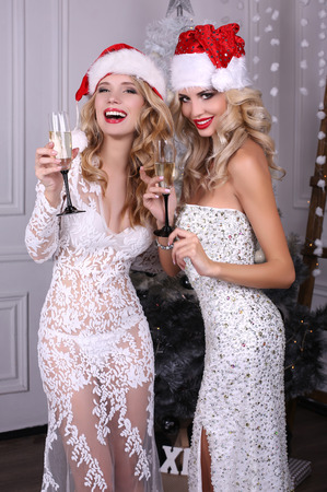 fashion interior photo of beautiful sexy girls with blond hair in luxurious dresses and Santa hat,holding glasses of champagne in hands,posing near Christmas tree Stock Photo