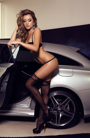 fashion photo of gorgeous woman with long blond hair wears luxurious lingerie,posing beside a car