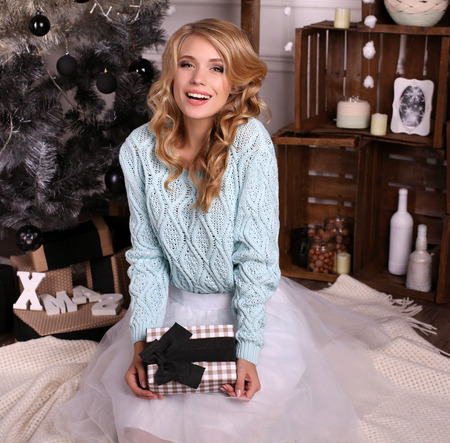 cabello rizado: moda foto interior de la hermosa joven con el pelo rubio y sonrisa encantadora, acogedora lleva cardigan de punto y falda fatin, posando al lado del árbol de Navidad y regalos