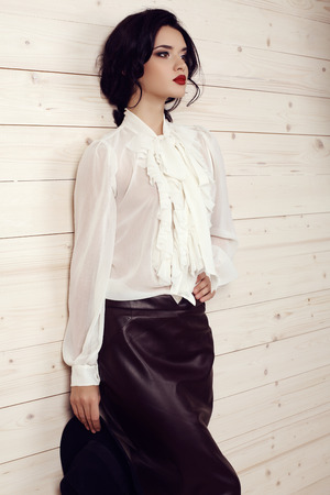 gorgeous woman: fashion studio photo of gorgeous young woman with dark hair and evening makeup,wears elegant clothes -white blouse, skirt and hat