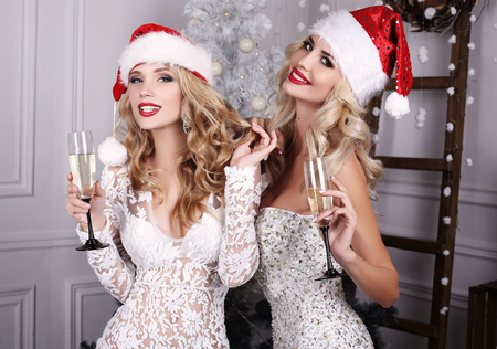 white dresses: fashion interior photo of beautiful sexy girls with blond hair wear luxurious party dresses and Santa hats,holding glasses with champagne in hands,celebrating New Year Stock Photo
