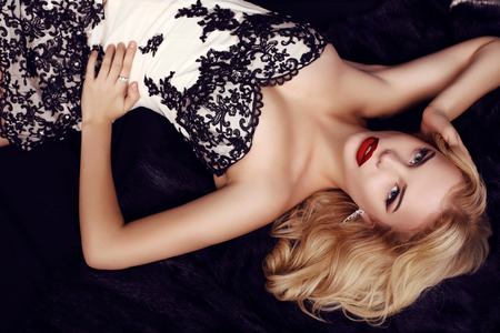 blonde woman: fashion studio photo of gorgeous sensual woman with blond hair and evening makeup,wears luxurious party dress and precious bijou,lying on fur coat Stock Photo