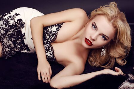 red lips: fashion studio photo of gorgeous sensual woman with blond hair and evening makeup,wears luxurious party dress and precious bijou,lying on fur coat Foto de archivo